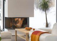 Moderní rodinný dům s dominantními střešními okny – obývací část s hořícím krbem.