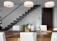 Moderní rodinný dům s dominantními střešními okny – pohled přes jídelní stůl na atypické schodiště.