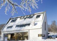 Moderní rodinný dům s dominantními střešními okny – pohled na boční stranu v zimě.