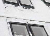 Moderní rodinný dům s dominantními střešními okny – detail zasněžených střešních oken.