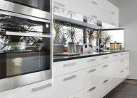 Moderní rodinný dům s dominantními střešními okny – detail bílé kuchyňské linky.