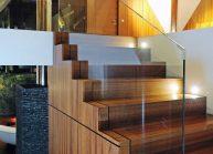 Venkovský rodinný dům od architekta Radomíra Grafka – detail dřevěného schodiště se skleněným zábradlím.